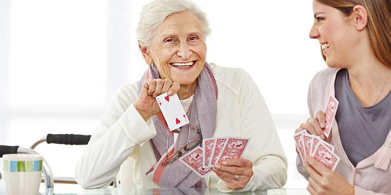Seniorin spielt Karten mit junger Frau
