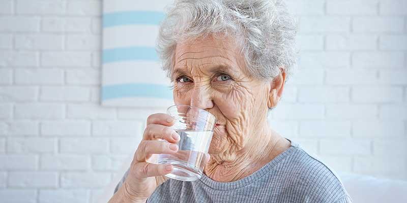 Eine Seniorin trinkt Wasser aus einem Glas