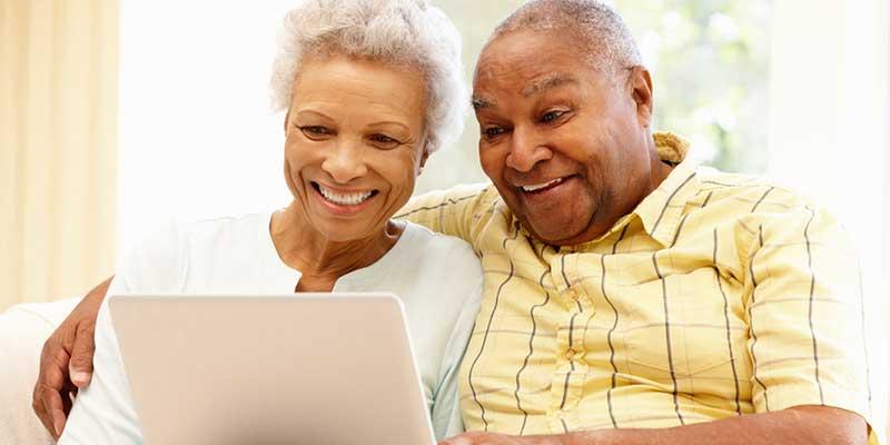 Älteres Pärchen begeistert mit Laptop.