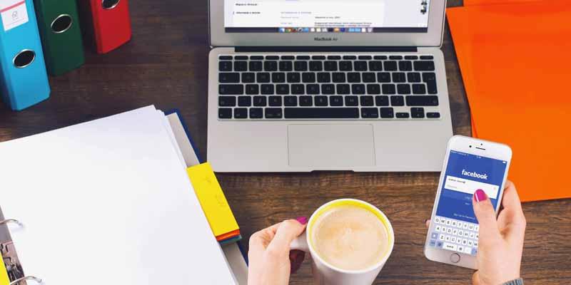 Büroarbeit & Facebook am Schreibtisch mit Notebook und Smartphone