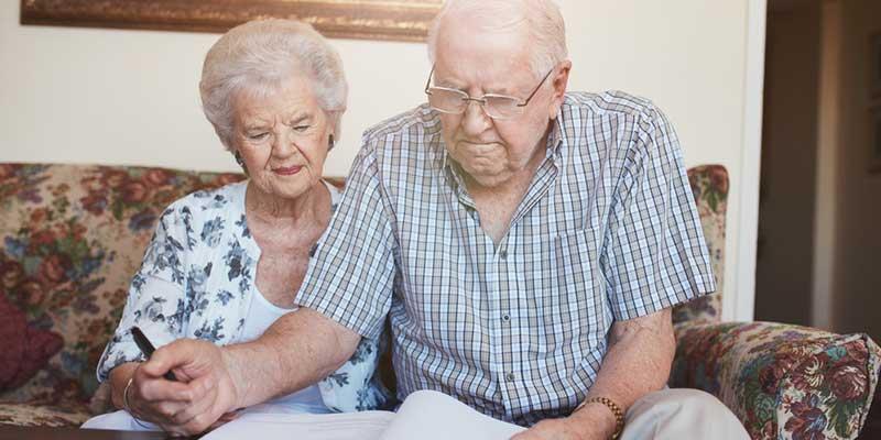 Älteres Paar beim Unterschreiben wichtiger Dokumente.