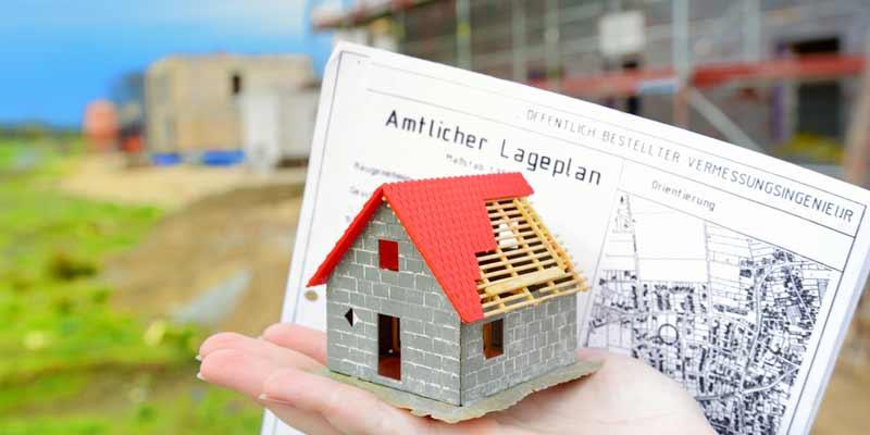 Ein Kind hält ein Spielzeughaus auf einer Baustelle in der Hand