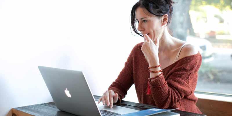 Frau sitzt vor einem Notebook