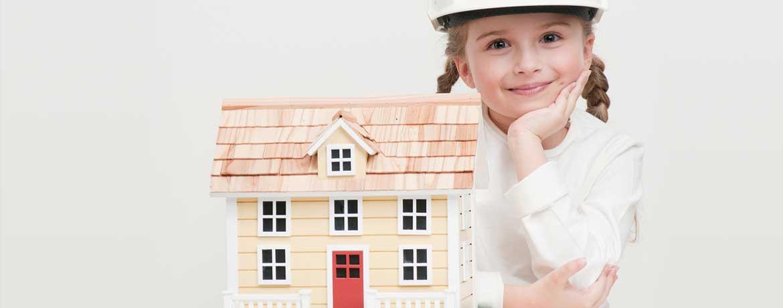Mädchen sitzt neben einem kleinen Haus