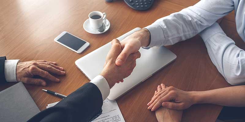 Zwei Personen reichen sich zum Vertragsabschluss die Hände.