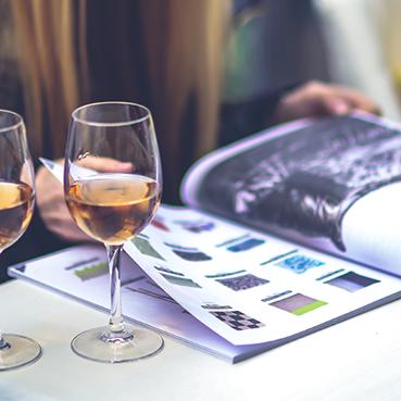 Junge Frau blättert in Magazin und trinkt dabei ein Glas Wein