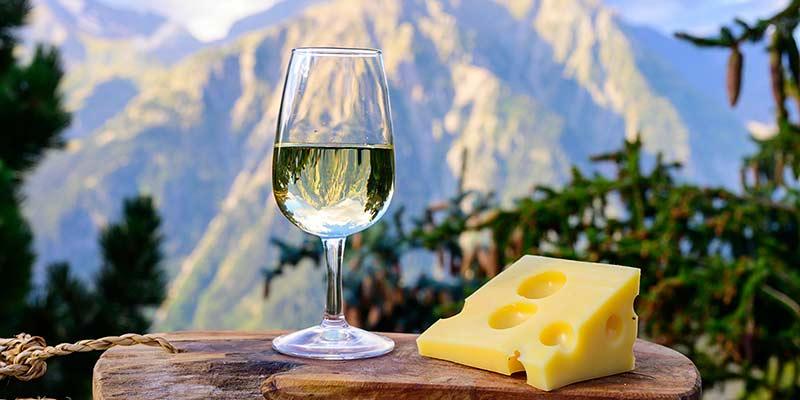 Genussvoller Weißwein und Käse vor einem Bergpanorama