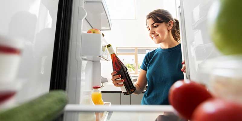Eine junge Frau holt eine Flasche Wein aus einem Kühlschrank