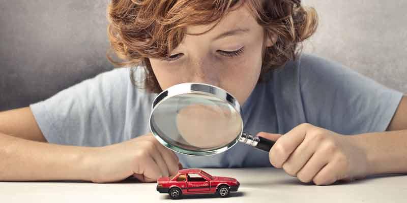 Junge schaut sich ein Spielzeugauto unter einer Lupe an