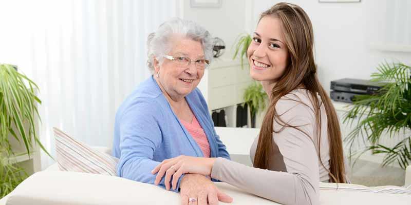 Seniorin und junge Frau sitzen auf einem Sofa